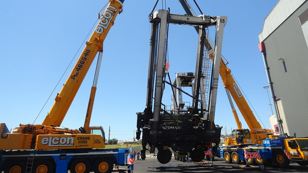 EASY DOES IT Two mobile cranes loaded the straddle carriers on their sides to be transported almost intact