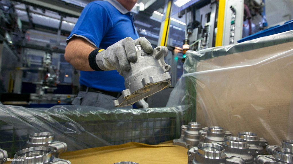 ON DUTY An employee holds a metal casing for an automotive steering system
