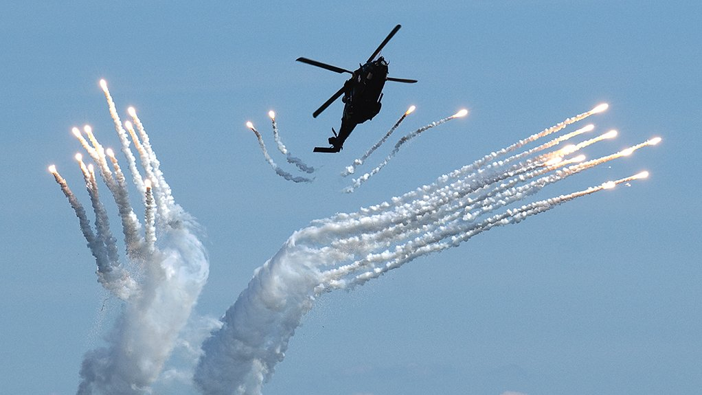A Swedish Air Force NH90 helicopter dispenses infrared countermeasure flares from a Saab Grintek Defence Integrated Defence Aids Suite