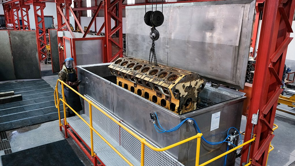 An engine block being lowered into the tank at Metric Automotive Engineering