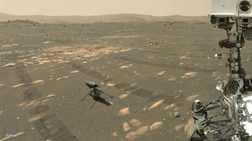 The Ingenuity drone helicopter (centre-left) sitting on the Martian surface, photographed by the Perseverance rover (part of which is visible on the right)
