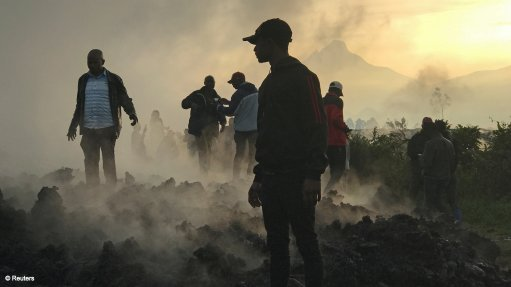 Residents walk near destroyed homes with the smouldering lava deposited by the eruption of Mount Nyiragongo volcano near Goma, in the DRC, May 23.