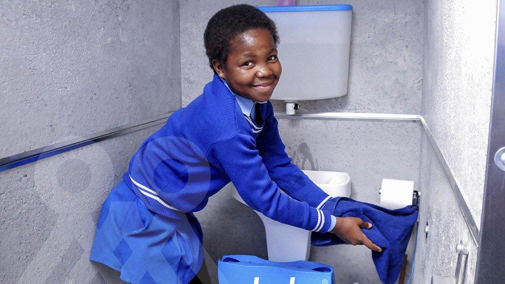 School girl washing hands inside the Amalooloo toilet