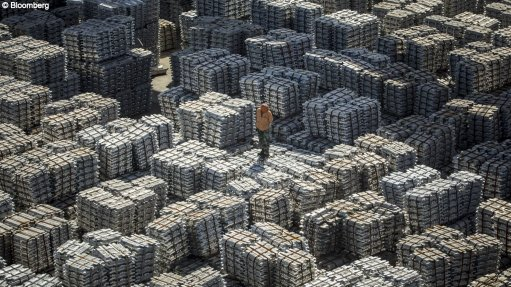 A worker stands on bundles of aluminum ingots at a China National Materials Storage and Transportation Corp. stockyard in Wuxi, China.