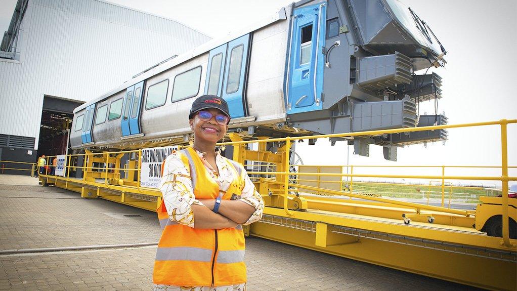 Gibela procurement executive Colette Yende stands outside in front of a train set at Gibela's premises