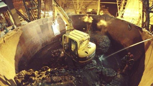 Mini excavator undertaking refractory demolition in a furnace