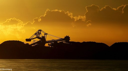 An image of a coal stacker against the setting sun at the Newcastle port, in Australia.