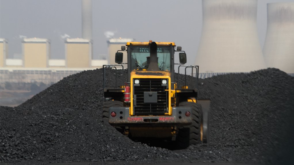 An image of a coal mining vehilce with a power station in the background.