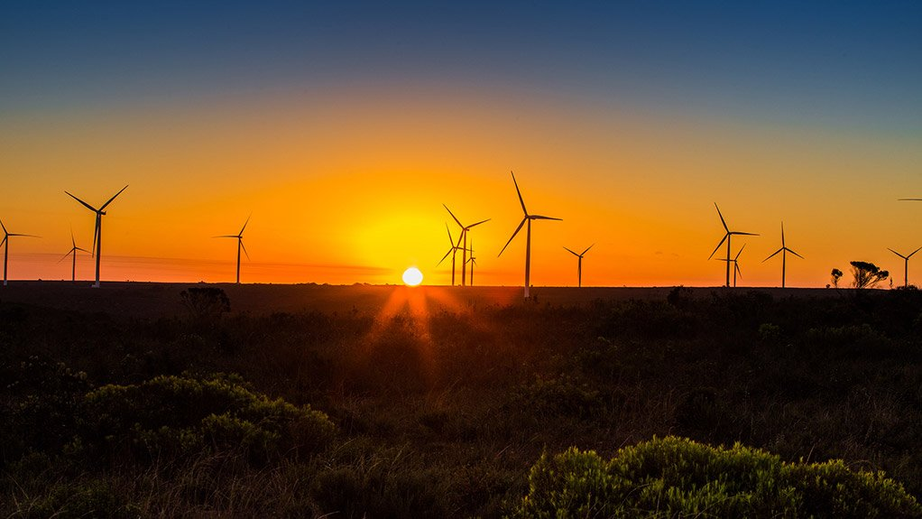 Image of sun rising behind wind turbines