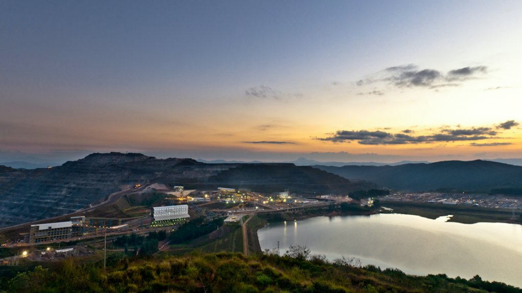An image of a mine waste dam and a processing plant in the background.