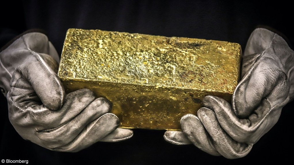 An image showing a person holding a gold bar.