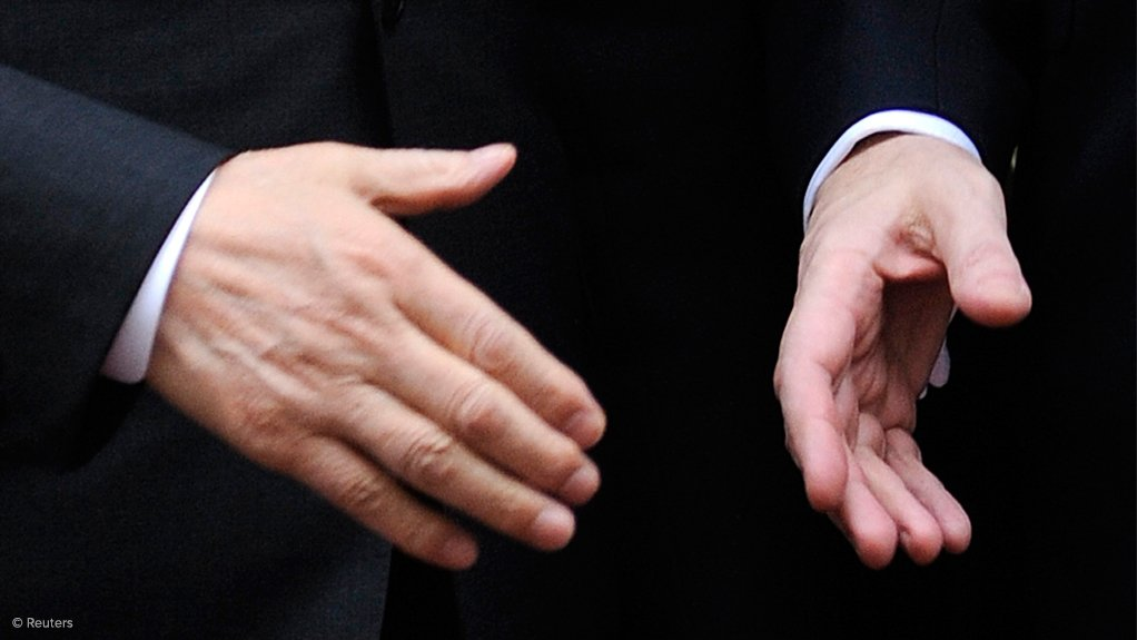 Image is a close-up of two hands about to shake