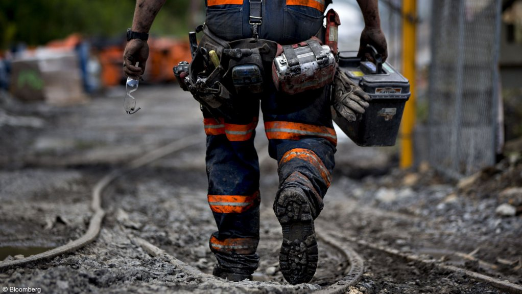 An image of a miner walking at a coal mine.