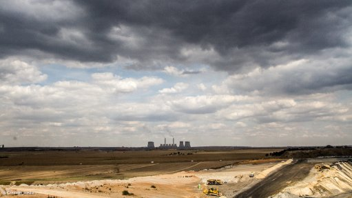 Photo of coal mining in the foreground with an Eskom power station in the background
