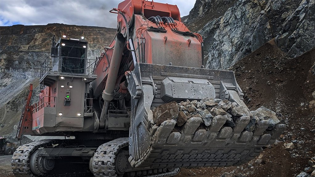 An image of a large red tracked front loader at the mine face with bucket full of ore ready to be graded by a ShovelSense system