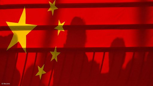 Image depicts the shadow of a man behind the Chinese flag
