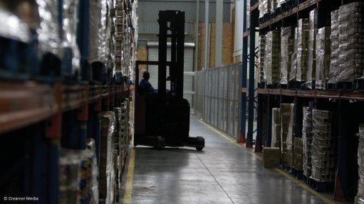 A photo of a forklift and driver operating in a shelved warehouse