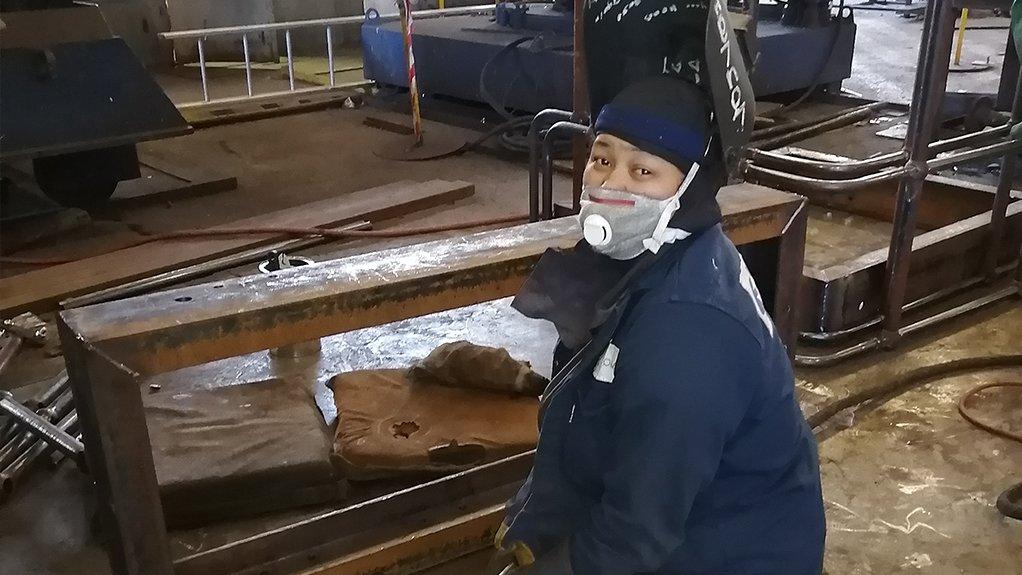 Woman welding on shop floor