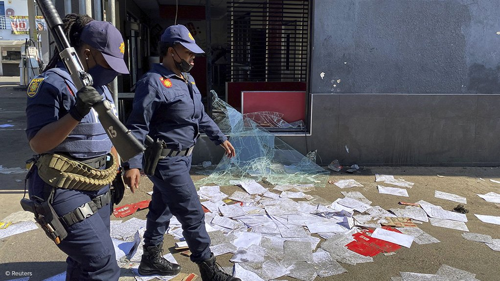 An image of police officers walking past property damaged in the July 2021 unrest in South Africa