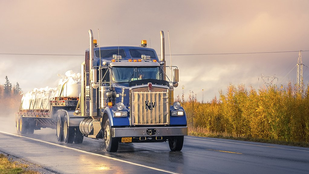 Blue truck driving on an open road.