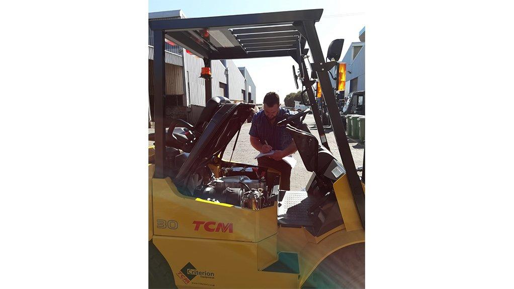 a man inspecting a forklift