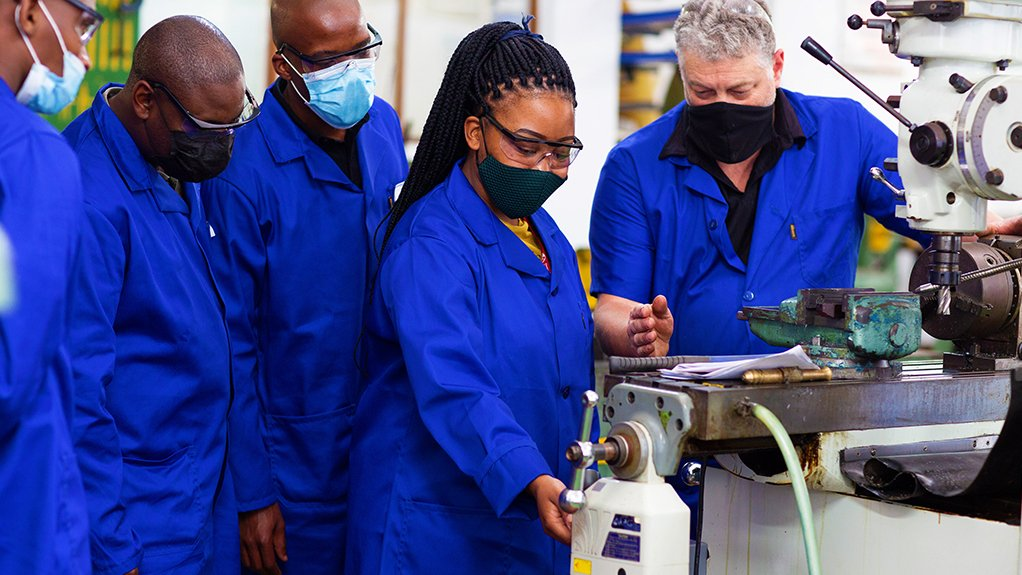 A photo young black men and women being trained by an older white man in an automotive component manufacturing facility