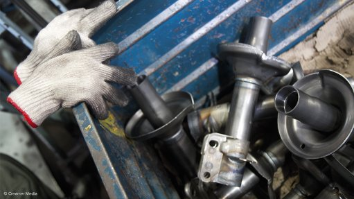 A photo of a pair of safety gloves resting on a skip filled with steel automotive components