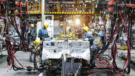 A photo of a high-tech automotive manufacturing facility and workers