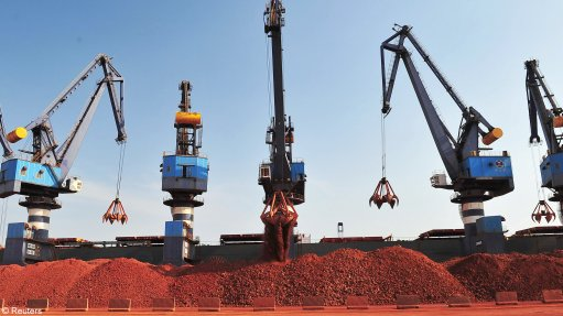 A ship carrying bauxite from Guinea is unloaded at a port.