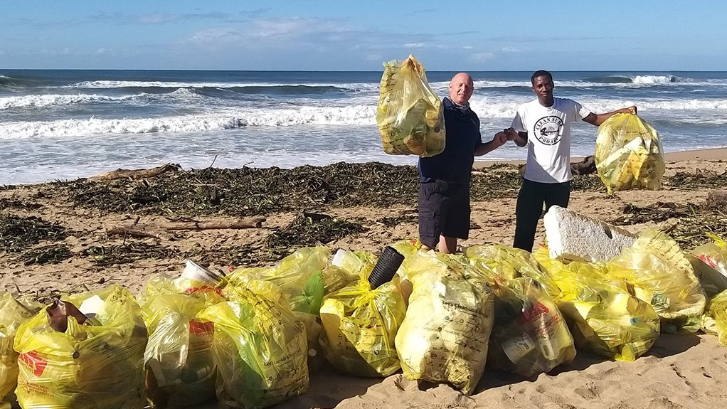A photo of Plastics SA sustainability director Douw Steyn and Clean Surf Project member Smphiwe Shozi picking up litter on a beach