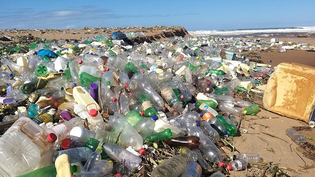 A photo of plastic bottles and other litter covering a beach