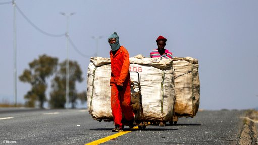 A photo of two informal waste reclaimers walking along the road dragging trolleys laden with recyclable waste