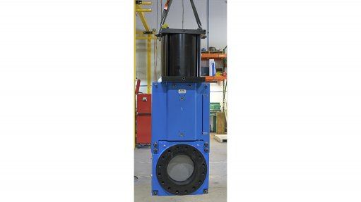 An image of a large blue high pressure valve used in tailings pipelines strung from a hoist