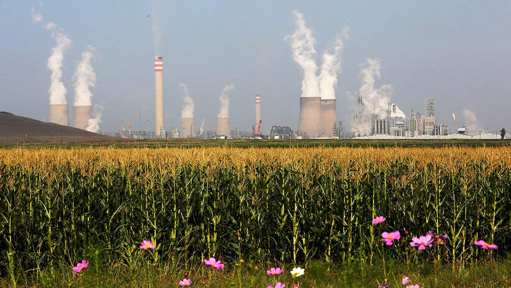 A photo of a Sasol plant emitting pollution into the air while crops and flowers grow in the foreground
