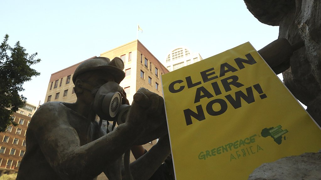 """A photo of a statue of a miner situated outside the Minerals Council South Africa offices that has been fitted with a gas mask with a Greenpeace Africa banner in front that reads """"CLEAN AIR NOW!"""""""