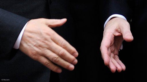 Image shows two hands shaking