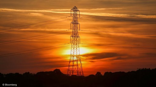An image of an electricity pylon against the setting sun.