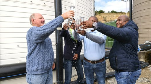 A photo of four people outside toasting one another with glasses of clean water at a water processing plant