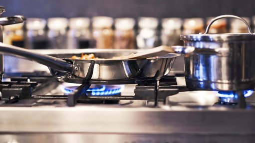 A stainless steel stove top with gas burners burning blue flame from an LPG gas supply, used for cooking
