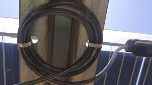 Picture of cables tied on a wall with clamps on either side