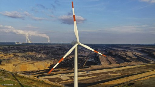 Image of a wind turbine with a coal mine and power station in the background.