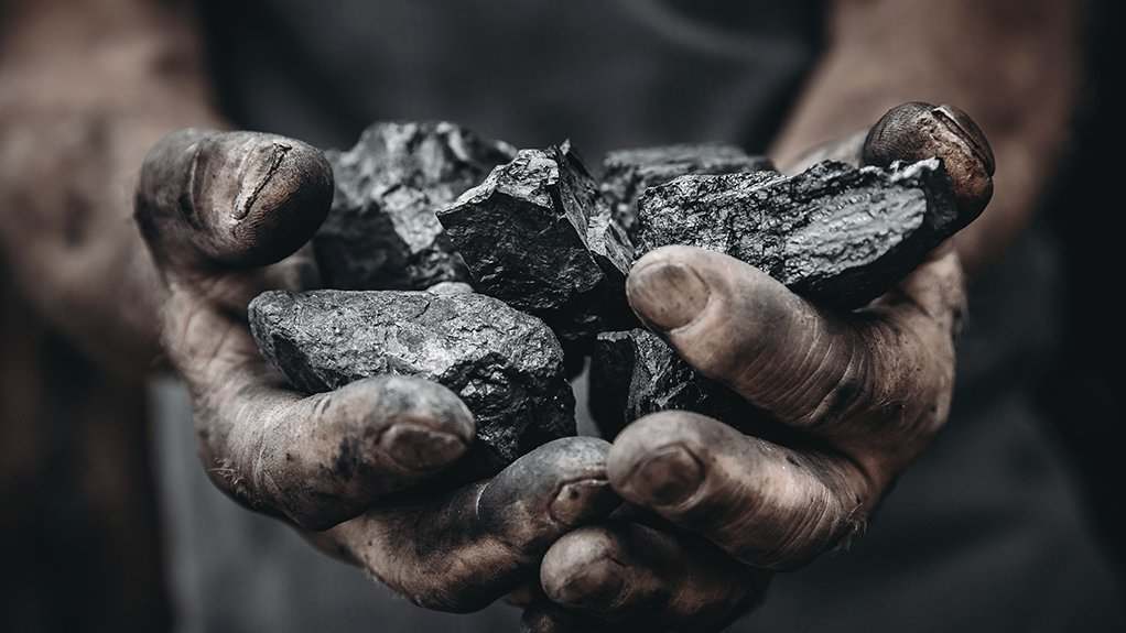 A photo of a miner holding coal in his hands