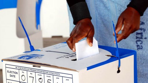 Image of a person inserting a ballot paper in the box