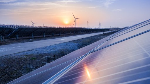 An image of solar PV panels and wind turbines